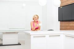 Taza del control de la mujer joven de cocina del café Fotos de archivo