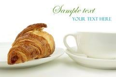 Taza del Croissant y de café en el fondo blanco Imagen de archivo libre de regalías