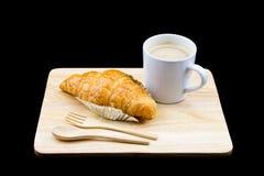 Taza del cruasán y de café con la bifurcación y la cuchara de madera imagen de archivo libre de regalías