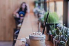 Taza del frappe del capuchino en la tabla con la chica joven borrosa que espera s Foto de archivo