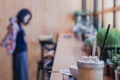 Taza del frappe del capuchino en la tabla con la chica joven borrosa que espera s Imagen de archivo libre de regalías