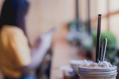 Taza del frappe del capuchino en la tabla con la chica joven borrosa que espera s Imagenes de archivo