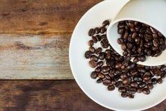 Taza del grano de café en la tabla fotografía de archivo libre de regalías