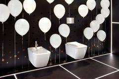 Taza del inodoro y bidé pendientes blancos modernos en interior del cuarto de baño negro con las bolas inflables blancas Fotos de archivo libres de regalías