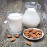 Taza del jarro y del vidrio con leche de la almendra imágenes de archivo libres de regalías
