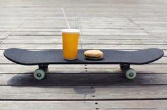 taza del jugo con la hamburguesa en un monopatín Imágenes de archivo libres de regalías