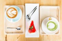 Taza del latte de la leche del té verde en la tabla de madera en cafetería Fotografía de archivo