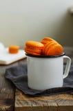 Taza del metal blanco por completo de galletas de color naranja de los macarrones Fotos de archivo