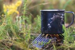 Taza del metal con el té que se calienta en la chimenea al aire libre hornilla seca del alcohol del brasero del alcohol foto de archivo