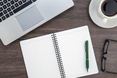 Taza del ordenador portátil, del cuaderno y de café en el escritorio del trabajo Imágenes de archivo libres de regalías