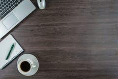 Taza del ordenador portátil, del cuaderno y de café en el escritorio del trabajo Fotos de archivo libres de regalías