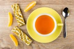 Taza del té, barras de granola con los cereales, rebanadas de naranja foto de archivo libre de regalías