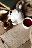 Taza del té con el dulzor siberiano - conos del azúcar, tetera y libros viejos en el fondo de madera, concepto de teatime acogedo imagen de archivo