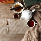 Taza del té con el dulzor siberiano - conos del azúcar, tetera y libros viejos en el fondo de madera, concepto de teatime acogedo fotografía de archivo