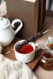 Taza del té con el dulzor siberiano - conos del azúcar, tetera y libros viejos en el fondo de madera, concepto de teatime acogedo imagen de archivo libre de regalías