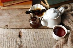 Taza del té con el dulzor siberiano - conos del azúcar, tetera y libros viejos en el fondo de madera, concepto de teatime acogedo fotos de archivo libres de regalías