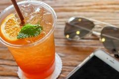 Taza del té de hielo del limón con la naranja y la menta en el top en el fondo hermoso de la textura de la corteza marrón con la  Fotografía de archivo libre de regalías