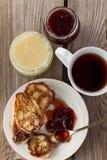 Taza del té, placa de crepes, atasco, miel Imagenes de archivo