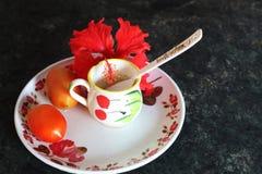 Taza del tomate y de té con la cuchara y la flor imagen de archivo