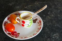 Taza del tomate y de té con la cuchara plástica en una placa plástica en la mesa de comedor imágenes de archivo libres de regalías