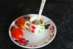 Taza del tomate y de té con la cuchara plástica en una tabla fotos de archivo