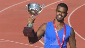 Taza del trofeo del deportista que se besa valeroso, celebrando triunfo y el reconocimiento metrajes