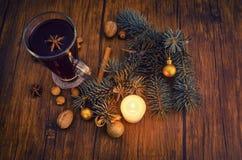 Taza del vino reflexionado sobre en una tabla de madera adornada con la vela, Foto de archivo libre de regalías