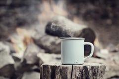Taza del vintage de café por una hoguera Foto de archivo libre de regalías