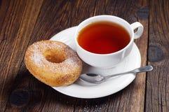 Taza dulce del buñuelo y de té Fotos de archivo libres de regalías