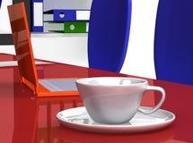 Taza en el escritorio de oficina cerca de la computadora portátil Foto de archivo libre de regalías