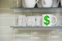 Taza en estante con símbolo del dólar Imágenes de archivo libres de regalías