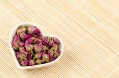 Taza en forma de corazón del té de los escaramujos (tratt del roxburghii de Rosa) en el suelo de bambú. Foto de archivo