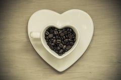 Taza en forma de corazón con los granos de café en la tabla de madera Fotos de archivo libres de regalías