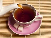 Taza en la cual vierta el té imagen de archivo libre de regalías