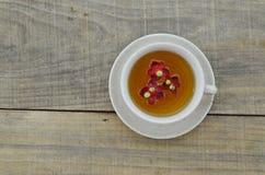 Taza encima del té aislado en la tabla de madera Imagenes de archivo