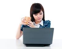 Taza femenina joven de la explotación agrícola y mirada de la computadora portátil Imagenes de archivo