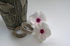 Taza grabada del metal con los anillos de bodas y las flores Imágenes de archivo libres de regalías