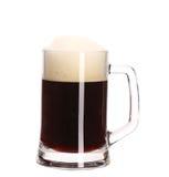Taza grande alta de cerveza marrón con espuma. Imagen de archivo libre de regalías