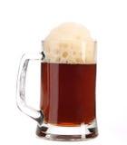 Taza grande alta de cerveza marrón con espuma. Foto de archivo