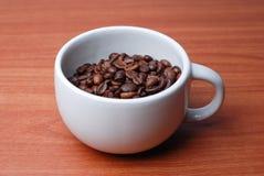 Taza grande llena de grano de café Imagen de archivo