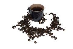 Taza gris de la arcilla de café asperjada con los granos del café en un whi Foto de archivo libre de regalías