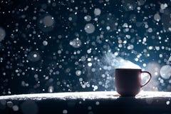 Taza hecha excursionismo de café caliente en fondo nevoso de la noche; Fotos de archivo
