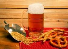 Taza helada de cerveza con los pretzeles y la cebada Imagenes de archivo