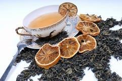 Taza herbaria de té con las hojas y los limones Foto de archivo libre de regalías