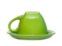 Taza invertida verde en un platillo. Imagen de archivo