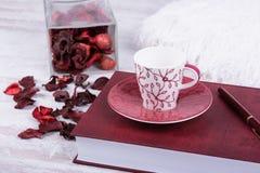 Taza, libro y pluma rojos de café en el fondo de madera blanco Foto de archivo