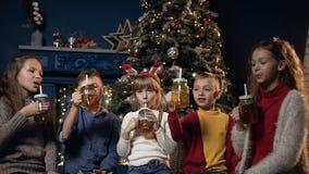 Taza linda de cinco alegrías de los niños de té en el fondo del árbol de navidad en sitio acogedor metrajes