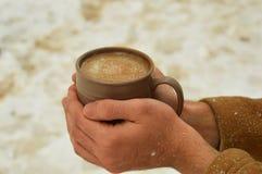 Taza masculina de la tenencia de la mano de caf? con el fondo nevoso fotografía de archivo libre de regalías