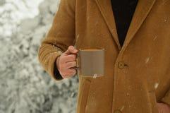 Taza masculina de la tenencia de la mano de caf? con el fondo nevoso imagen de archivo libre de regalías