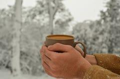 Taza masculina de la tenencia de la mano de caf? con el fondo nevoso imágenes de archivo libres de regalías